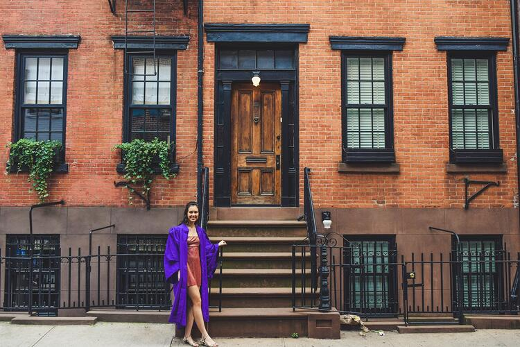 Proud international student in front of their NYC apartment
